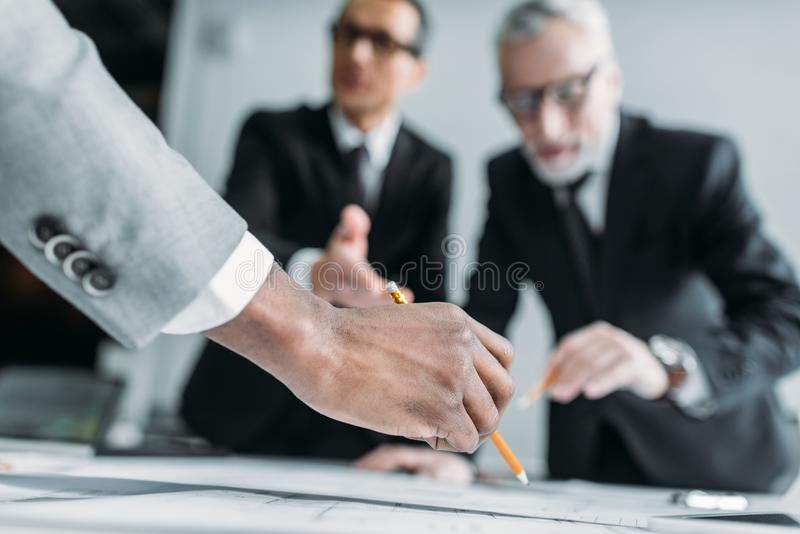 Partial view of multicultural businessmen at meeting. In office royalty free stock photos