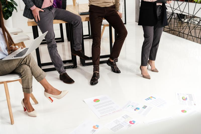 Partial view of multicultural group of marketing managers with papers on floor. In office royalty free stock photography