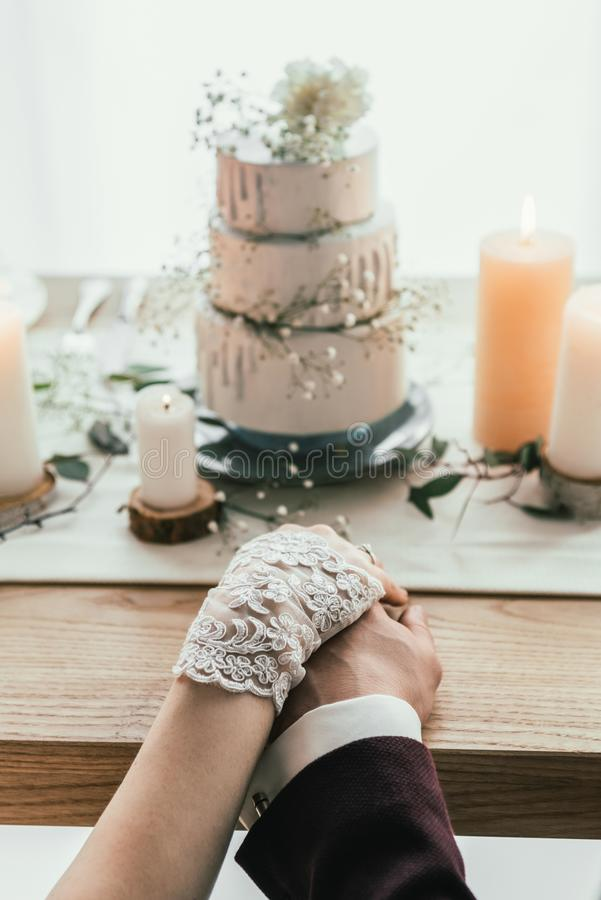 partial view of newlyweds holding hands while sitting at served table with wedding cake, rustic stock photos