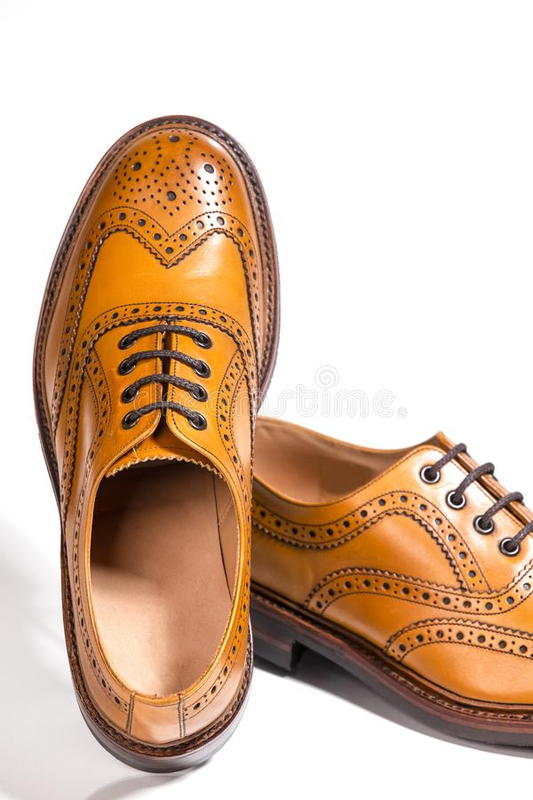 Partial View of Pair of Luxury Male Full Brogued Tan Oxford Shoe. S. isolated Over White Background.Vertical Composition stock images