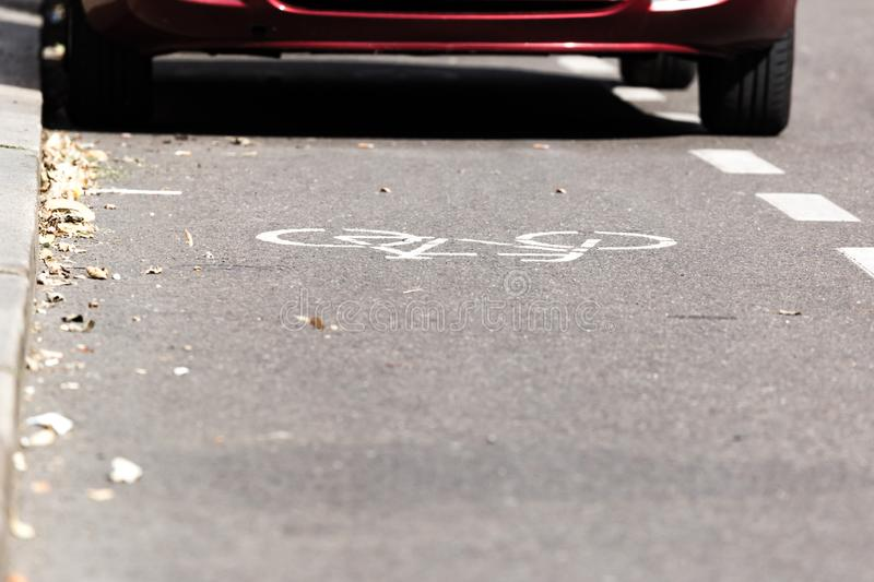 Partial view of a parked car on a bike path.  stock photography