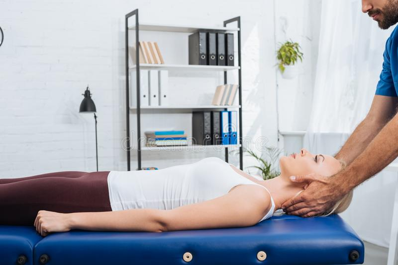 Partial view of physiotherapist massaging neck of patient that lying on massage table. In clinic royalty free stock image