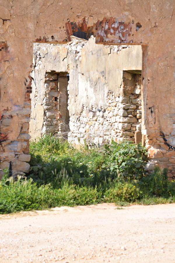 Partial view of a ruined house. With green grass in front royalty free stock photo