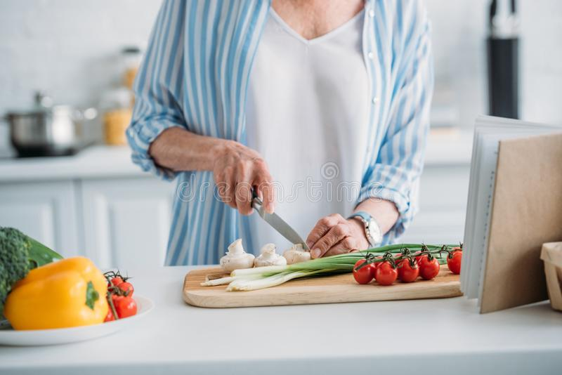 Partial view of senior lady cutting mushrooms while cooking dinner at counter in kitchen royalty free stock images