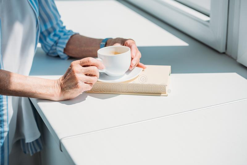 partial view of senior woman with book and cup of coffee on windowsill at home stock photos