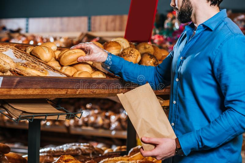 partial view of shopper taking loaf of bread stock images