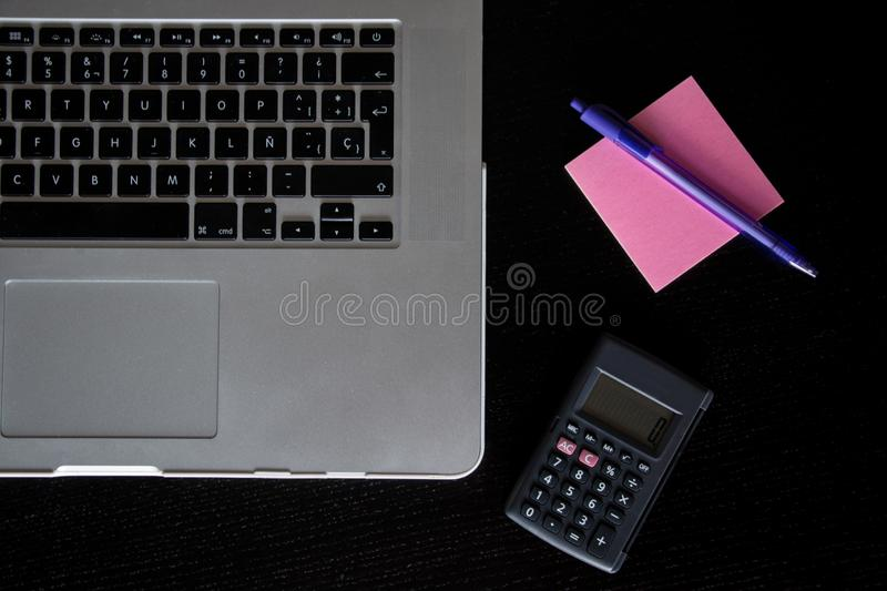 Partial view of a silver keyboard of a laptop with a calculator, and a pink post-it notes with a pencil on a dark wood desk stock image
