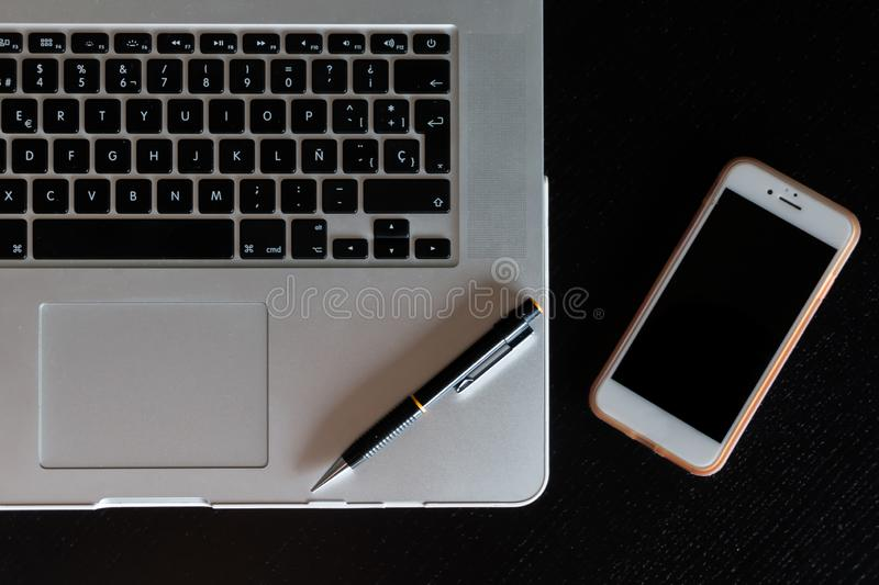 Partial view of a silver keyboard of a laptop with a smartphone and a pencil on a dark wood desk.  royalty free stock photography