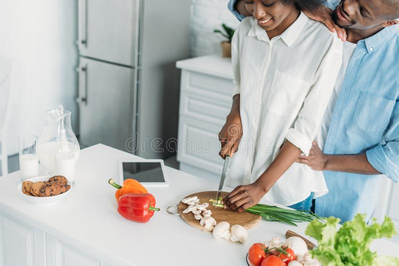 Partial view of smiling african american cooking breakfast together in kitchen. At home royalty free stock image
