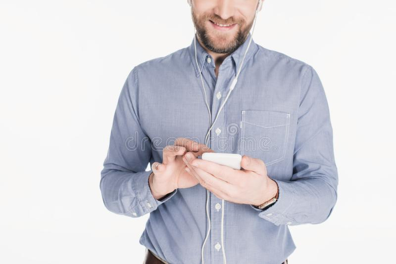 partial view of smiling bearded man in earphones using smartphone royalty free stock photography