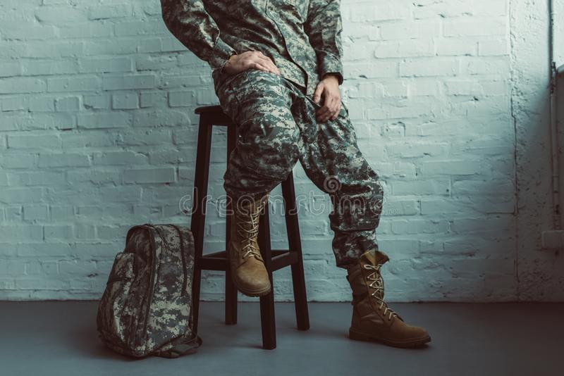Partial view of soldier in military uniform sitting on chair against white. Brick wall royalty free stock photos