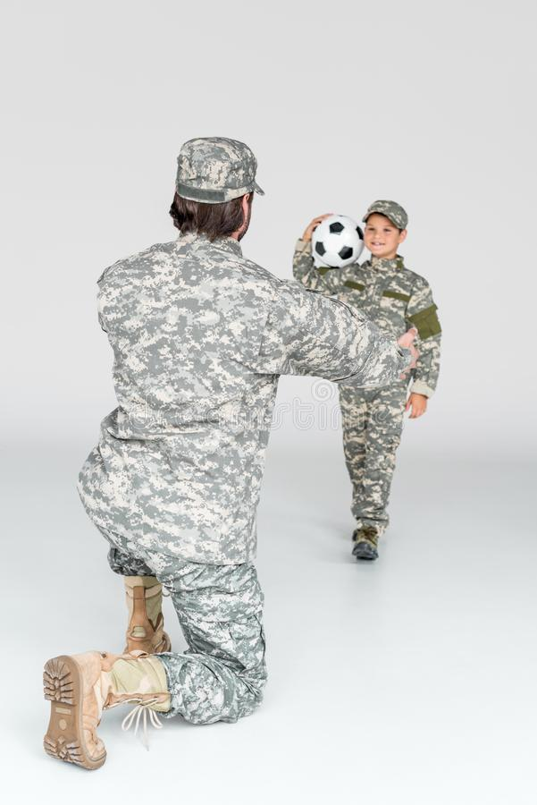 partial view of soldier with outstretched arms and smiling kid in camouflage clothing with soccer ball royalty free stock photo