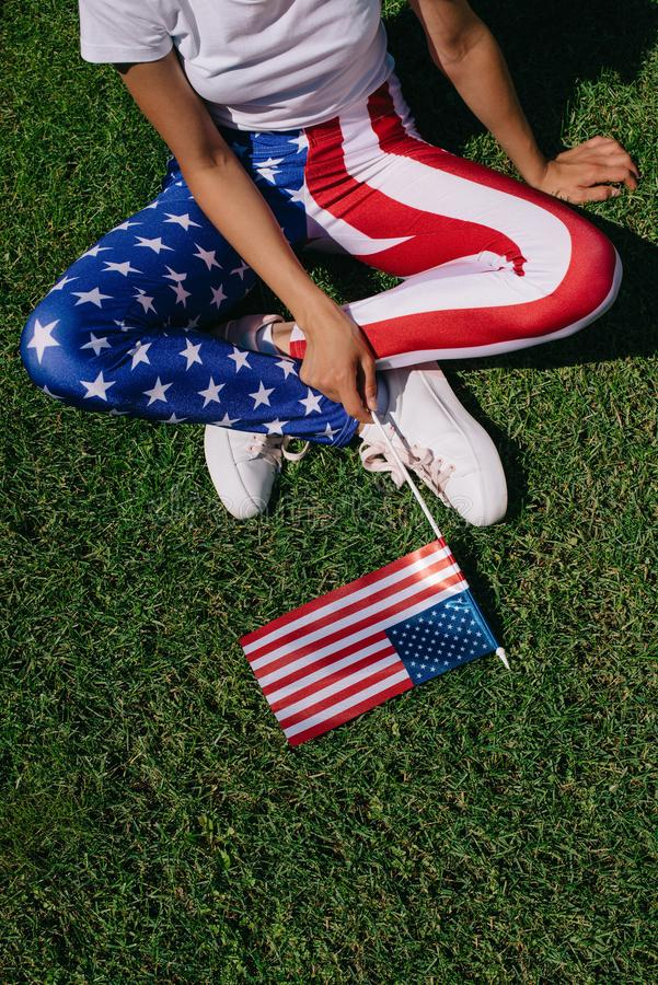 Partial view of woman with flagpole in leggins with american flag pattern resting on green lawn, americas independence day. Holiday concept royalty free stock photography