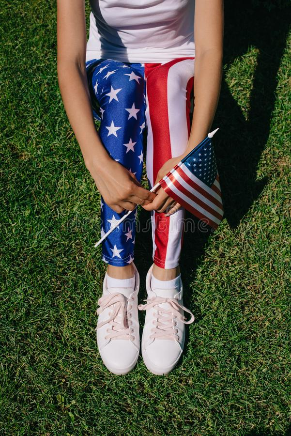 Partial view of woman with flagpole in leggins with american flag pattern resting on green lawn, americas independence day. Holiday concept royalty free stock photo