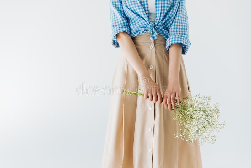 Partial view of woman holding bouquet of flowers in hands. Isolated on grey royalty free stock photos
