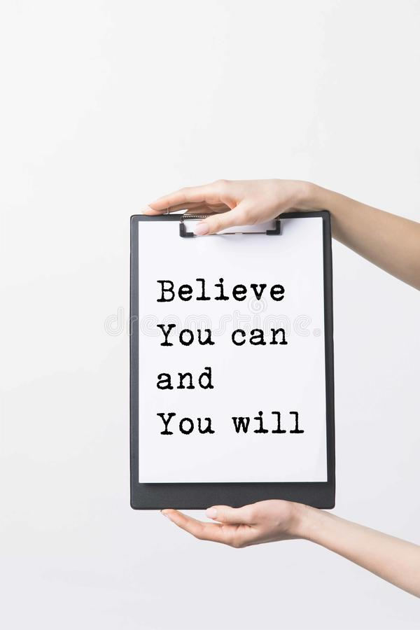 Partial view of woman holding clipboard with Believe You can and You will inspiration in hands. Isolated on white royalty free stock photography