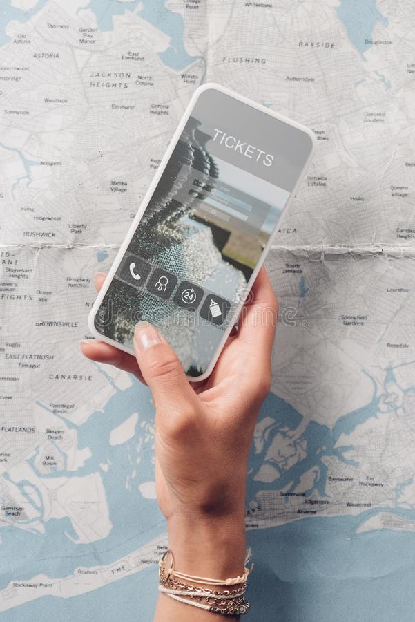partial view of woman holding smartphone with tickets website on screen and map stock photography