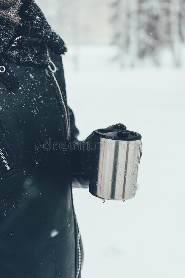 Partial view of woman holding thermocup with hot drink. On winter day royalty free stock image