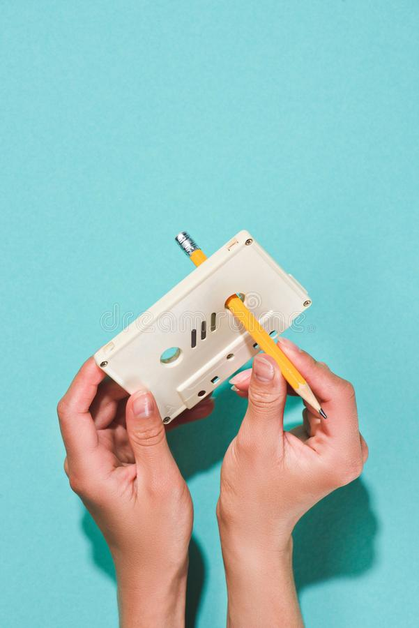 partial view of woman holding white retro audio cassette and pencil stock photo