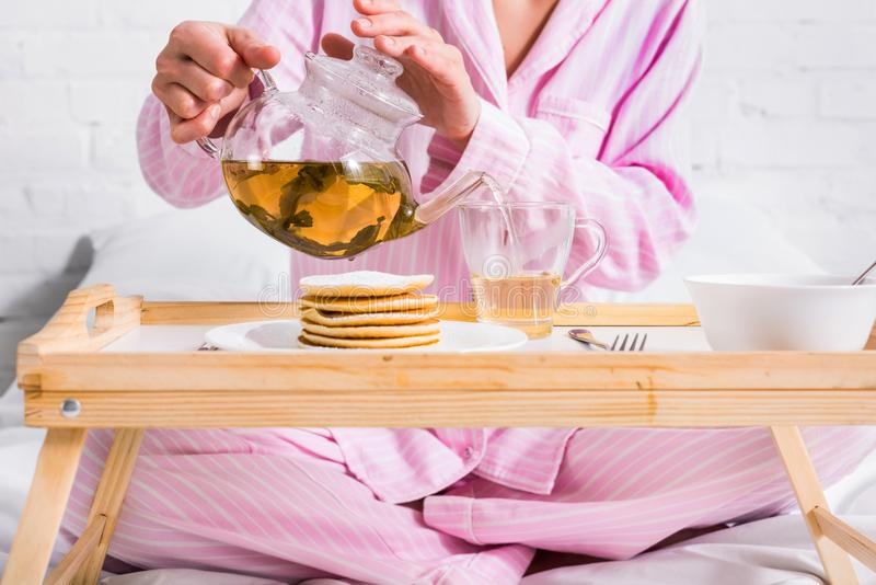 Partial view of woman in pink pajamas pouring green tea into cup while having breakfast in bed. At home royalty free stock photo
