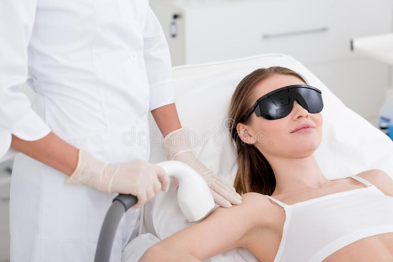partial view of woman receiving laser hair removal procedure on arm made by cosmetologist royalty free stock photos