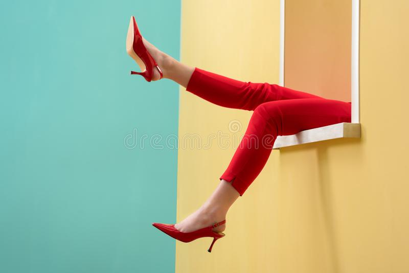 Partial view of woman in red pants and shoes outstretching legs out decorative window stock photography