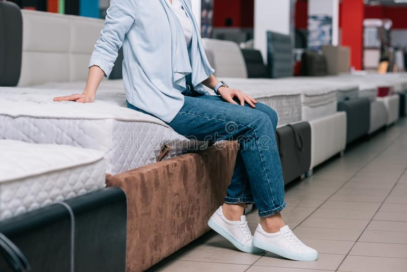 partial view of woman sitting on mattress royalty free stock images