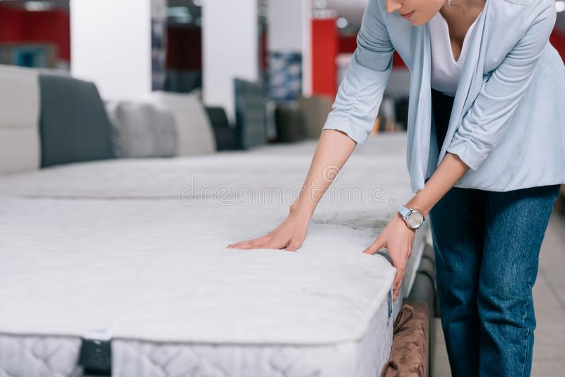 partial view of woman touching orthopedic mattress stock images