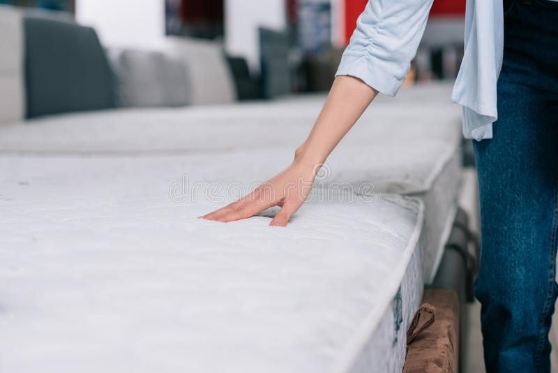 Partial view of woman touching orthopedic mattress. In furniture shop stock photography