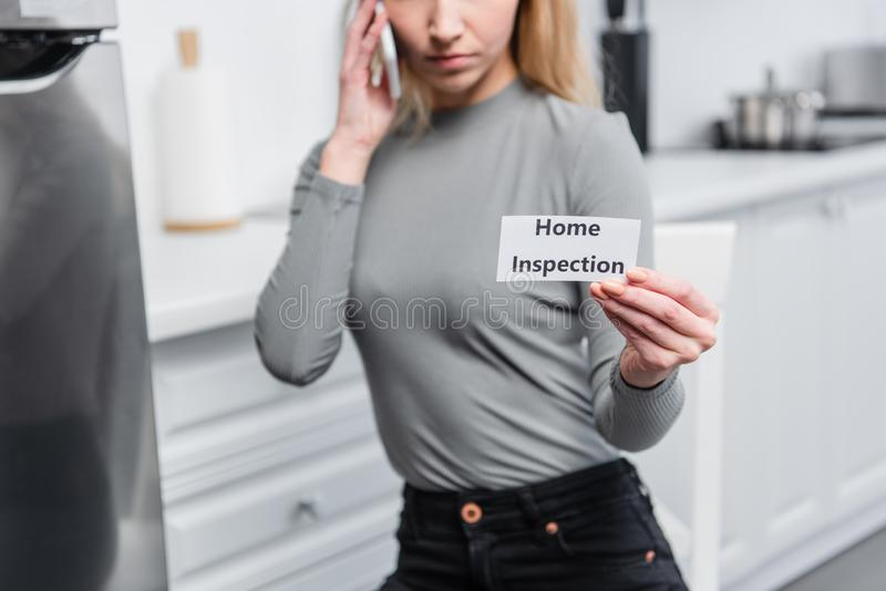 Partial view of young woman holding card with lettering home inspection and talking on smartphone. In kitchen stock image