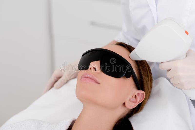 Partial view of young woman. Receiving laser hair removal epilation on face in salon royalty free stock photos