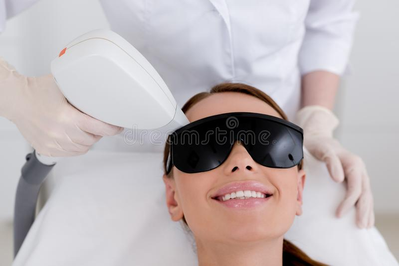 Partial view of young woman. Receiving laser hair removal epilation on face in salon stock image
