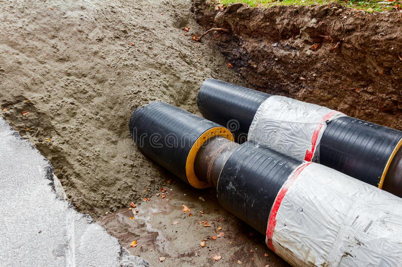 Partially buried pipeline. Work in progress, burying pipeline in a urban area royalty free stock photo