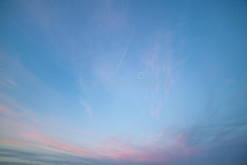 Partially Cloudy Pastel Pink and Purple Dusk Light with Blue Sky.  stock photography