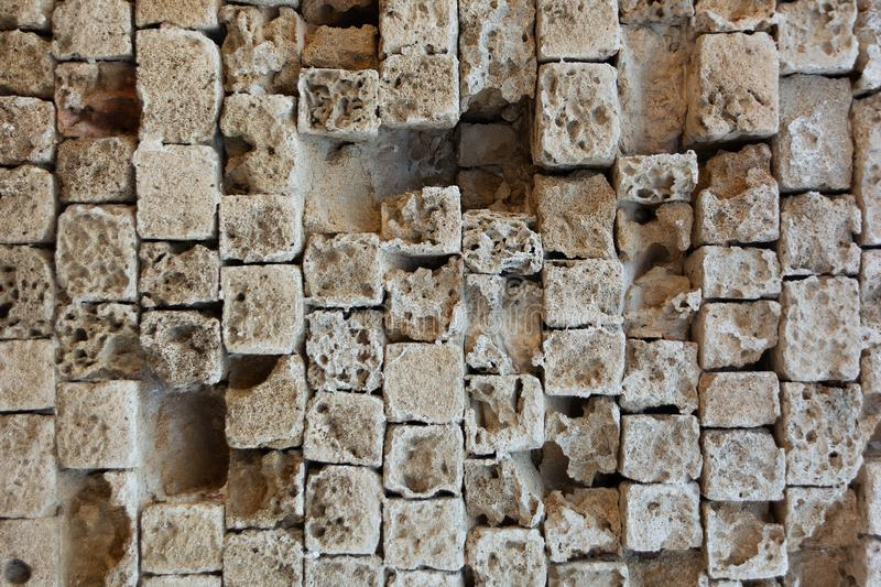 Partially destroyed masonry wall of old stone blocks of limestone. Background texture of weathered ancient brick wall stock images