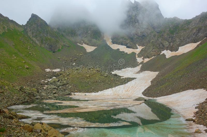 Partially frozen Didighali lake with a mountain pass in the background on a hiking trail in Caucasus mountains leading to Silver L stock photography