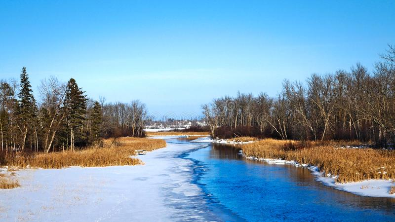 Partially frozen Mississippi River flows north toward Bemidji Minnesota in winter stock photography