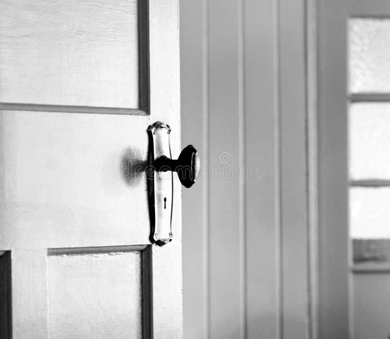Partially opened vintage interior door - concept behind closed doors stock photography