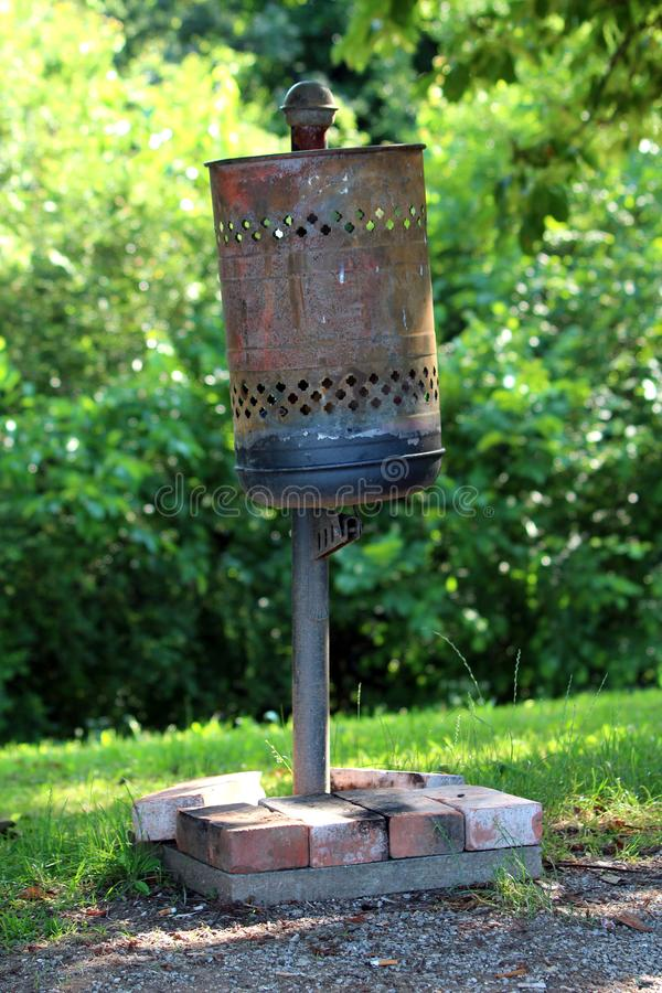 Partially rusted old dilapidated metal public trash can held in place with concrete foundation covered with small red bricks in. Local park on warm sunny spring royalty free stock photo