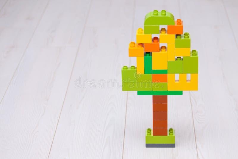Particelle elementari di plastica multicolori nella forma dell'albero su fondo leggero Istruzione e concetto d'apprendimento iniz fotografie stock