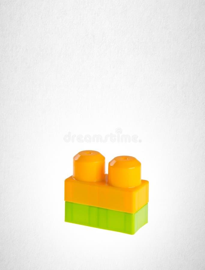 Particelle elementari o blocchetti di plastica di Lego su un fondo fotografie stock