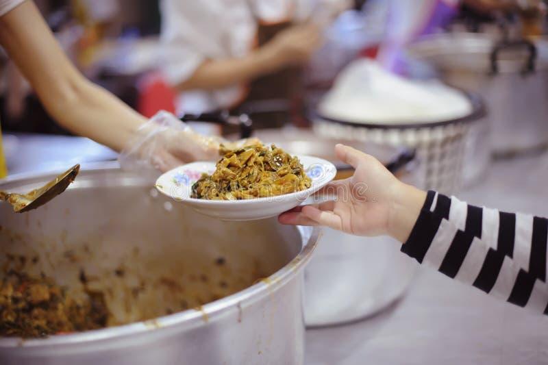 Participação em compartilhar o alimento para os pobres: o conceito da falta de alimentos no mundo fotos de stock