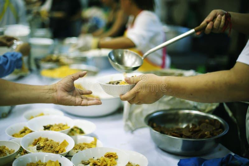 Participação em compartilhar o alimento para os pobres: o conceito da falta de alimentos no mundo fotos de stock royalty free