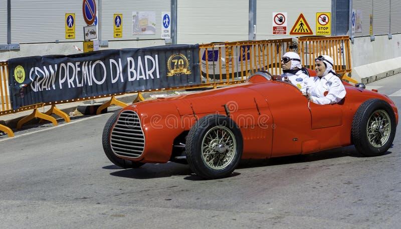 Participant à sa voiture de course à la concurrence dans la reconstitution historique image libre de droits