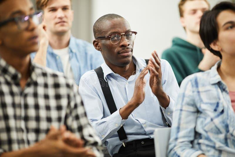 Participant de conférence africain applaudissant pour le haut-parleur photo stock