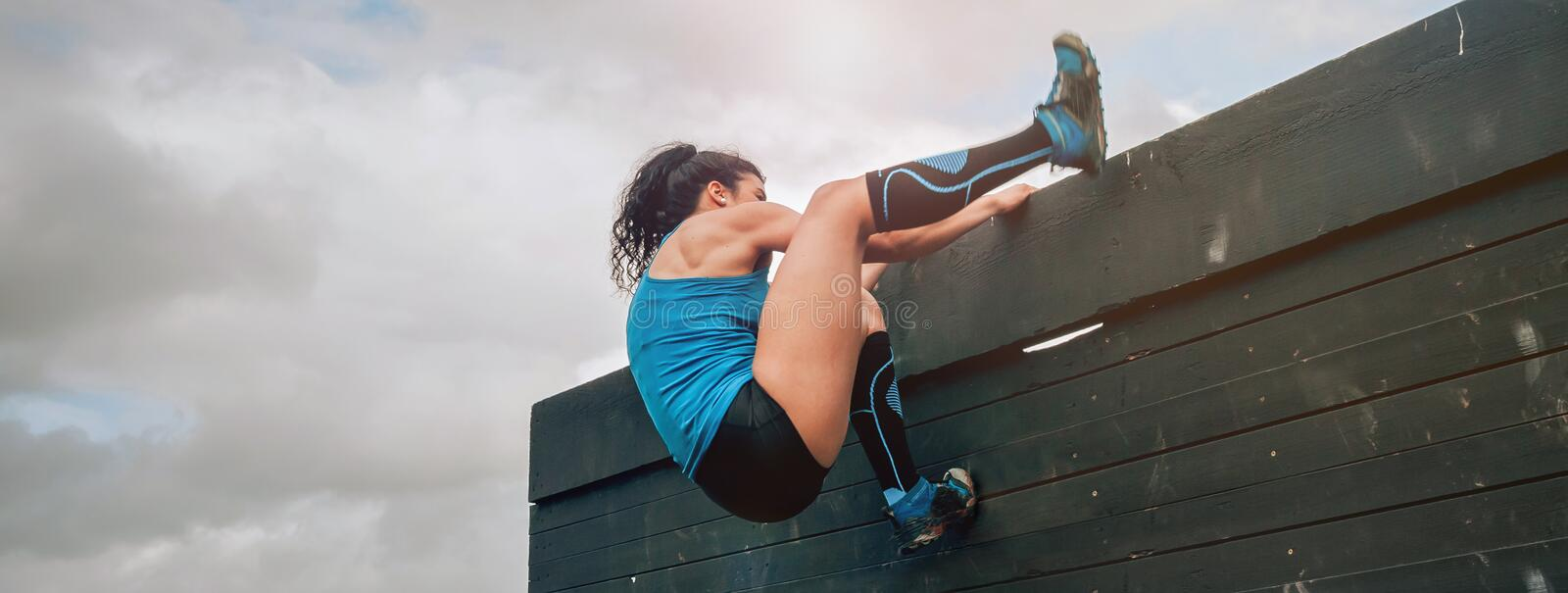 Participant in obstacle course climbing wall. Female participant in an obstacle course climbing a wall royalty free stock photography