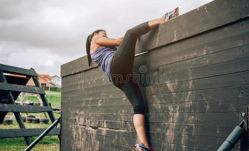 Participant in obstacle course climbing wall. Female participant in an obstacle course climbing a wall stock photo