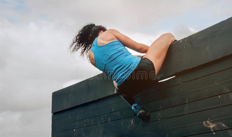 Participant in obstacle course climbing wall. Female participant in an obstacle course climbing a wall stock image