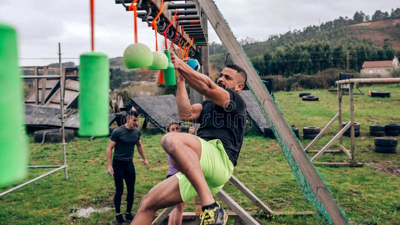 Participant obstacle course doing suspension. Male participant in an obstacle course doing suspension exercises stock image