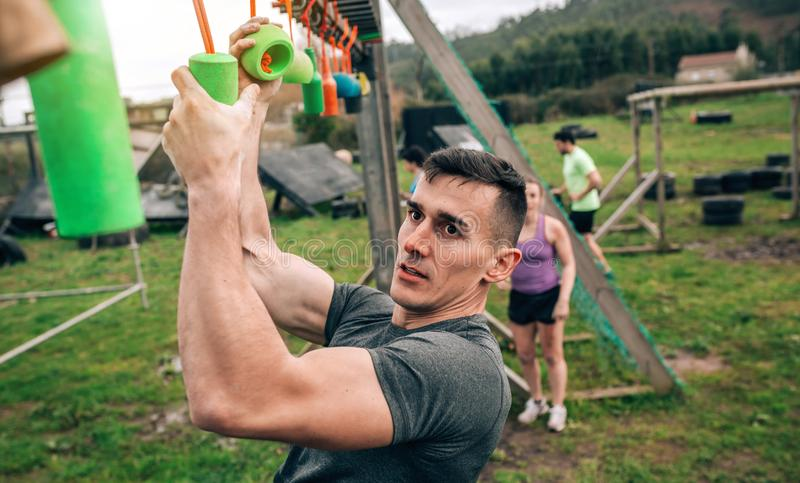Participant obstacle course doing suspension. Male participant in an obstacle course doing suspension exercises royalty free stock photography